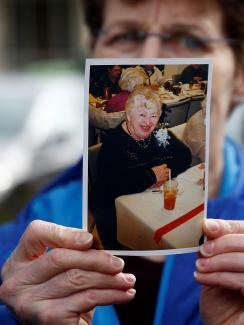 The image shows pat holding a picture of her mother partially in front of her face. Even though her face is partly obscured, Pat looks very distraught. Elaine in the photo is smiling warmly. This is a powerful and sad photo.