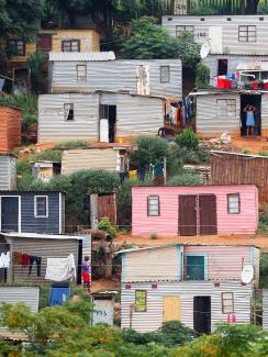 The photo shows a hillside covered with tin shacks, some colorfully painted.