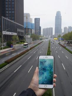 This is a striking photo with the phone held in the foreground looking out on a vast expanse of empty urban road.