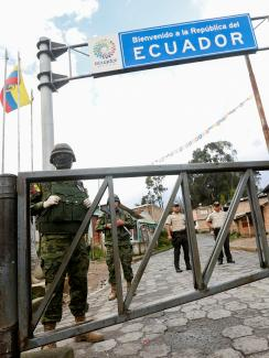 The photo shows a border crossing with a large sign reading, Ecuador, and several soldiers in the frame.