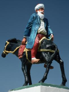 Photo shows a statue of the famous figure riding backward on a donkey.