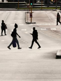 This is a stunning photo showing a broad main thoroughfare that is completely bereft of cars. Four people are seen crossing the wide street, each silhouetted against the early or late sun reflecting off the asphalt pavement.
