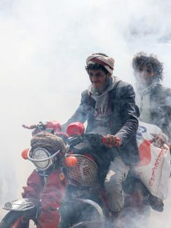 This is a powerful photo showing two men on one motorbike driving through a thick cloud of disinfectant mist.