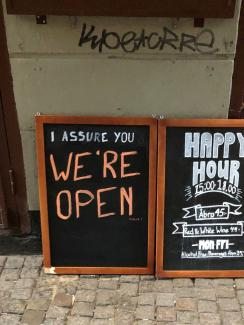 "Picture Shows two side-by-side chalk placards in front of a restaurant advertising a happy hour inside. One of the signs reads, ""I assure you WE'RE OPEN."""