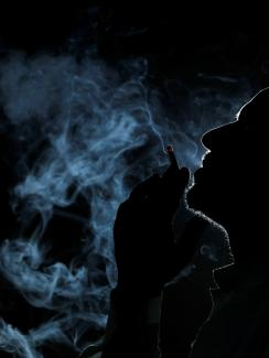 The image shows a dark silhouette of a man in profile smoking and filling the air around him with smoke.
