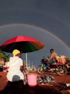 This is a spectacular photo that shows a woman under a bright red umbrella from behind as she is sitting on the side of the road greeting passer-bys with a full-double rainbow highlighting a storm-darkened sky in the distance.
