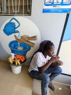 Picture shows a girl with a small basket of fruit sitting next to a large, blue UNICEF basin.