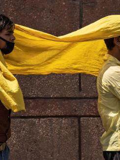 The image shows two men sharing a yellow scarf.