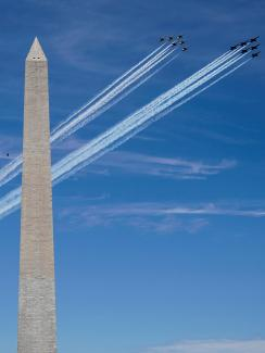 The photo shows two tight formations of several jets flying by the Washington monument on a brilliant blue sky day.