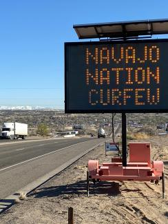 "Picture shows a portable electronic road warning sign programmed to display the message ""NAVAJO NATION CURFEW."""