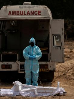 The photo shows a man dressed entirely in protective gear with his head bowed in font of an ambulance and before what appears to be a corpse wrapped in white sheets.