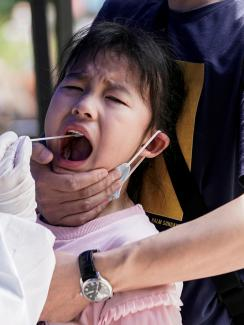 The photo shows the child being gripped by an adult while a health worker swabs a sample from her mouth. She appears to be screaming.