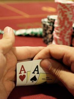 Photo shows a pair of hands holding up the corners of two cards to reveal a pair of aces. A large stack of chips is in the background.