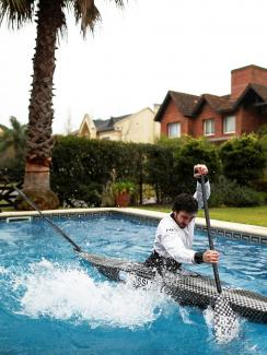 The photo shows the canoeist rowing furiously in a swimming pool.