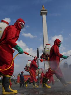 Photo shows several workers in bright red protective suits walking though an open area spraying from tanks they carry on their backs. A monument can be seen in the background.