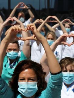 The photo shows a large number of health workers standing together and holding up a heart symbol above their heads.