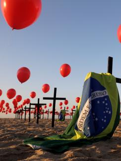 The photo shows an art installation of crosses, balloons and flag on the beach.