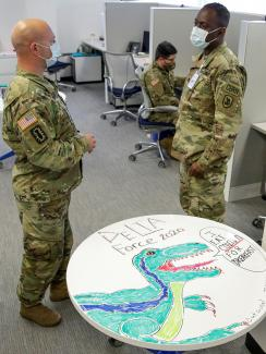 "The photo shows the guard members standing around a cubicle space talking. A table in the foreground is decorated with a drawing of a dinosaur and emblazoned with the words ""I eat COVID-19 for breakfast."