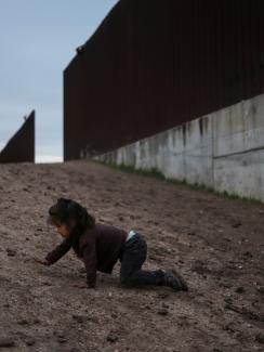 The photo shows a small child crawling on the ground near a giant border fence.