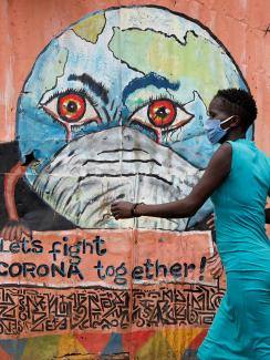 This is a striking photo of a woman in a blue dress wearing a facemask walking past a peach-colored wall with a graffiti of the Earth, also wearing a facemask, with bloodshot eyes and crying.