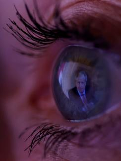 The photo shows a macro lens image of an eye with the image of the PM reflected in it.