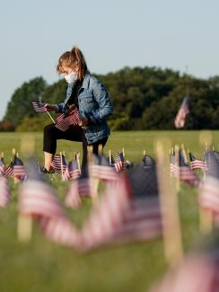 The photo shows a young woman on one knee planting a small American flag in the ground. Many more can be seen blurred and out of focus in the foreground.