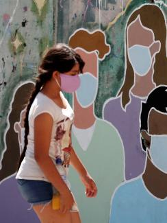 A girl wearing a face mask to prevent the spread of the coronavirus disease (COVID-19) walks past a graffiti in homage to the medical staff, at the San Martin hospital, in La Plata, on the outskirts of Buenos Aires, Argentina January 21, 2021.