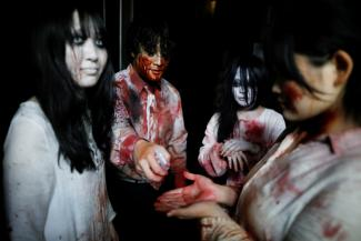 Actors dressed as zombies disinfect their hands before their performance at a drive-in haunted house show by Kowagarasetai (Scare Squad) in Tokyo, Japan on July 3, 2020.