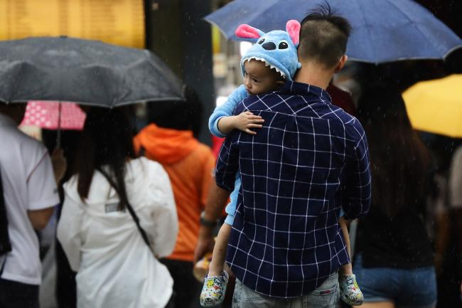 A parent carrying a child dressed in cartoon themed pajamas crosses a street in the rain in Singapore on January 10, 2021.