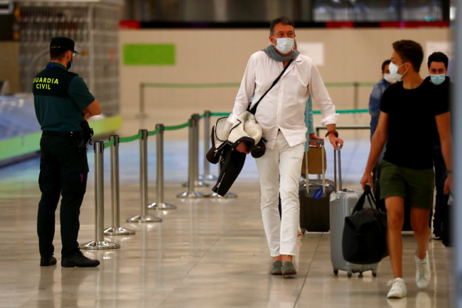 Guardia Civil officer watches as passengers, wearing protective face masks, walk upon arrival from Paris at Adolfo Suarez Barajas airport as Spain reopens June 2020